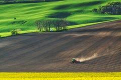 Il trattore agricolo tratta la terra sul campo Fotografia Stock Libera da Diritti