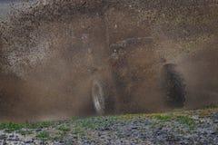 Il trattore all'alta velocità si muove attraverso un grande fango profondo, creante una grande nuvola di spruzzo Fotografia Stock Libera da Diritti