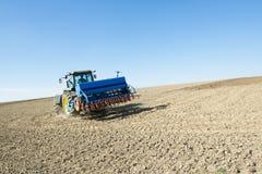 Il trattore ara i solchi su un campo Immagini Stock Libere da Diritti