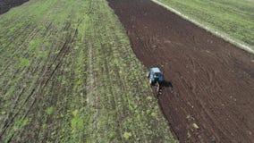 Il trattore ara la terra dell'azienda agricola stock footage