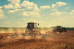 Il trattore ara un campo Immagine Stock