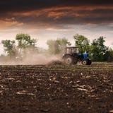 Il trattore ara un campo in primavera contro un bello cielo del tramonto Fotografia Stock Libera da Diritti