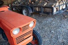 Il trattore arancio accanto ad una traccia ha caricato con i ceppi fotografia stock