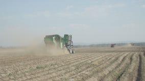 Il trattore blu con una macchina per la raccolta delle patate va sul campo archivi video