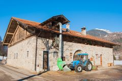 Il trattore blu si è fermato accanto ad un'azienda agricola con le pareti rocciose immagine stock