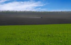 Il trattore coltiva il campo Fondo rurale rurale Vista panoramica del paesaggio della molla un giorno soleggiato con un campo del Fotografia Stock Libera da Diritti
