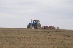 Il trattore coltiva il suolo in primavera Fotografie Stock