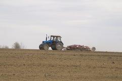 Il trattore coltiva il suolo in primavera Fotografia Stock Libera da Diritti