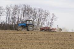 Il trattore coltiva il suolo in primavera Fotografia Stock