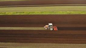 Il trattore coltiva la terra nel campo Immagini Stock