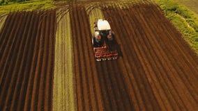 Il trattore coltiva la terra nel campo Fotografie Stock Libere da Diritti