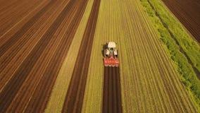 Il trattore coltiva la terra nel campo Immagine Stock