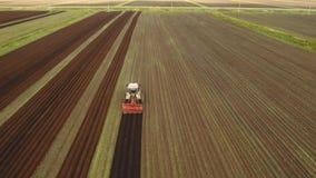 Il trattore coltiva la terra nel campo Immagini Stock Libere da Diritti