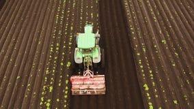 Il trattore coltiva la terra nel campo stock footage