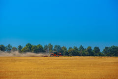 Il trattore del giorno di estate tira un aratro sul campo di pendenza di grano Fotografia Stock