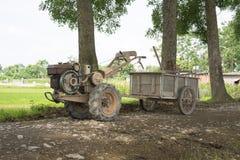 Il trattore dell'aratro trasforma al piccolo vagone per i prodotti di trasporto dell'agricoltura Immagini Stock