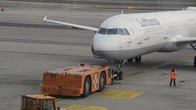 Il trattore di Push-Back rimorchia gli aerei di Lufthansa Airbus A-321-200 a partire dal portone video d archivio