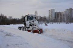 Il trattore di Snowy di un servizio municipale getta la neve dai passaggi pedonali nel parco della città sulla mattina dell'inver Fotografie Stock