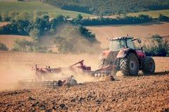 Il trattore e la stoppia arano in un campo raccolto Fotografia Stock