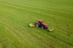 Il trattore falcia l'erba su una vista aerea verde del campo fotografie stock