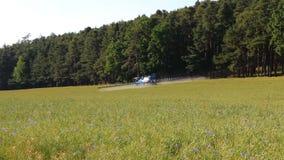 Il trattore fertilizza il campo vicino alla foresta, concetto dell'agricoltura, repubblica Ceca video d archivio