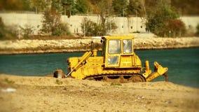 Il trattore giallo del bulldozer solleva la sabbia sulla spiaggia video d archivio