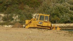 Il trattore giallo del bulldozer solleva la sabbia sulla spiaggia archivi video