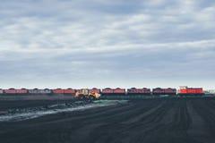 Il trattore giallo guida sul campo e sul sorpasso del treno Immagini Stock