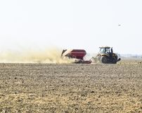 Il trattore guida sul campo e trasforma il fertilizzante il soi Fotografia Stock