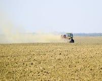 Il trattore guida sul campo e trasforma il fertilizzante il soi Immagini Stock