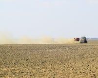 Il trattore guida sul campo e trasforma il fertilizzante il soi Fotografie Stock