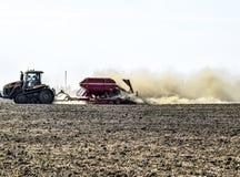 Il trattore guida sul campo e trasforma il fertilizzante il soi Fotografie Stock Libere da Diritti