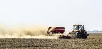 Il trattore guida sul campo e trasforma il fertilizzante il soi Fotografia Stock Libera da Diritti