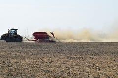Il trattore guida sul campo e trasforma il fertilizzante il suolo Fertilizzanti dopo l'aratura del campo Immagine Stock Libera da Diritti