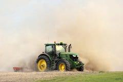 Il trattore harrows il campo in una nuvola di polvere enorme Fotografia Stock