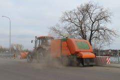 Il trattore lava e pulisce la polvere e la sporcizia delle vie Immagini Stock