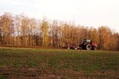 Il trattore nel campo ara la terra in autunno Fotografia Stock