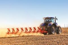 Il trattore prepara il terreno per la semina e la coltivazione Agr Immagine Stock