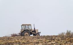 Il trattore prepara un campo per seminare Fotografia Stock