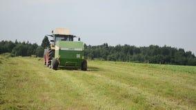 Il trattore raccoglie il giacimento del fieno stock footage