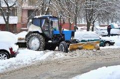 Il trattore rimuove la neve in cortile Immagini Stock