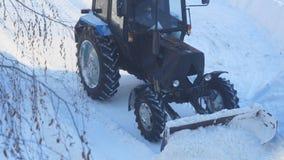 Il trattore rimuove la neve dalla strada stock footage