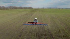 Il trattore sta funzionando nel campo in molla in anticipo Produce straziante per impedire la perdita del suolo di umidità antenn stock footage