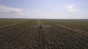 Il trattore sta spruzzando il giacimento della patata dei fertilizzanti Video aereo stock footage