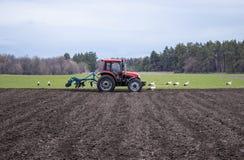 Il trattore tratta la terra Gli agricoltori preparano la terra per la semina dei semi fotografia stock libera da diritti