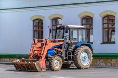 Il trattore variopinto con un secchio è vicino alla casa Fotografie Stock