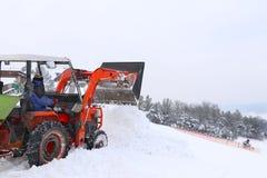 Il trattore versa la neve con il suo secchio sul pendio dello sci Il lavoro del gatto delle nevi nell'orario invernale Preparazio immagini stock libere da diritti