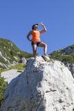 Il trekker della donna beve su nelle montagne Immagini Stock Libere da Diritti