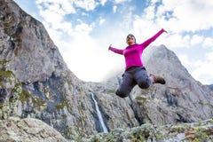 Il trekker della donna sta stando contro la cascata delle alte montagne nel Ca Fotografie Stock Libere da Diritti