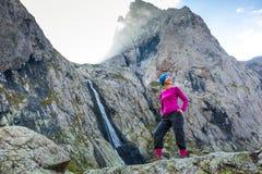 Il trekker della donna sta stando contro la cascata delle alte montagne nel Ca Fotografia Stock Libera da Diritti